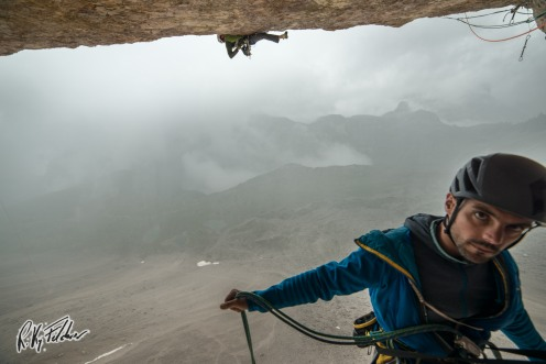 "Trying the crux pitch of ""Pan Aroma"" (Tre Cime) in the rain - Credits: Riky Felderer"